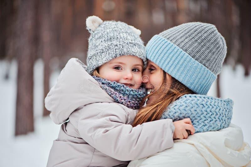 Gelukkige moeder en dochter op de gang in de sneeuwwinter stock afbeelding