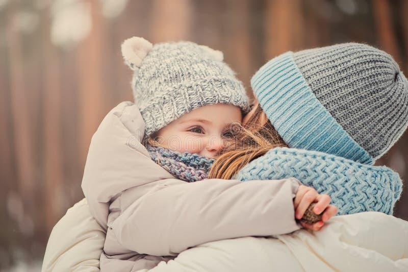 Gelukkige moeder en dochter op de gang in de sneeuwwinter royalty-vrije stock foto