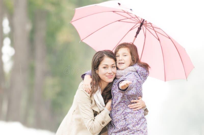 Gelukkige moeder en dochter in park in regen. royalty-vrije stock foto's