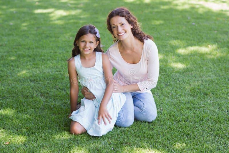 Gelukkige moeder en dochterzitting op het gras stock foto's