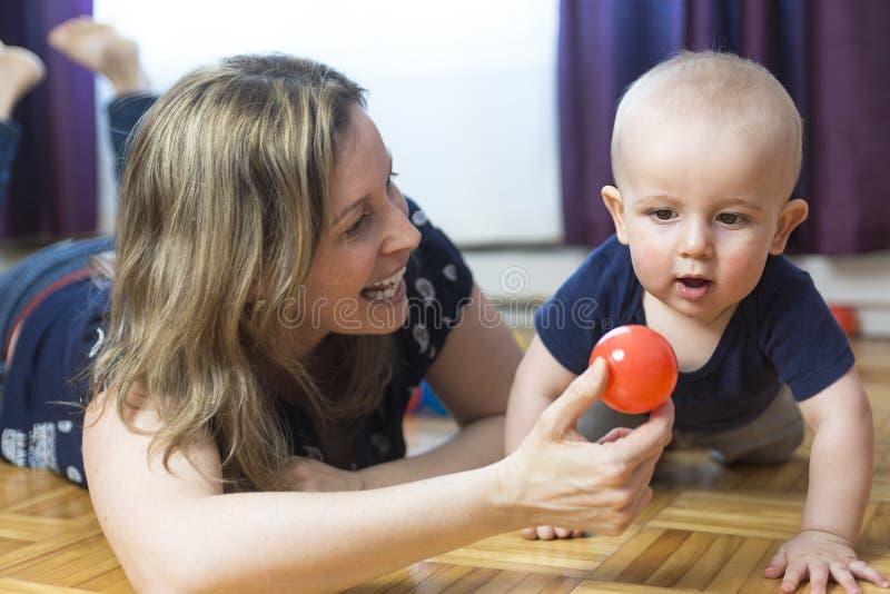 Gelukkige moeder en haar 1 éénjarigezoon het spelen met kleine bal thuis stock foto's