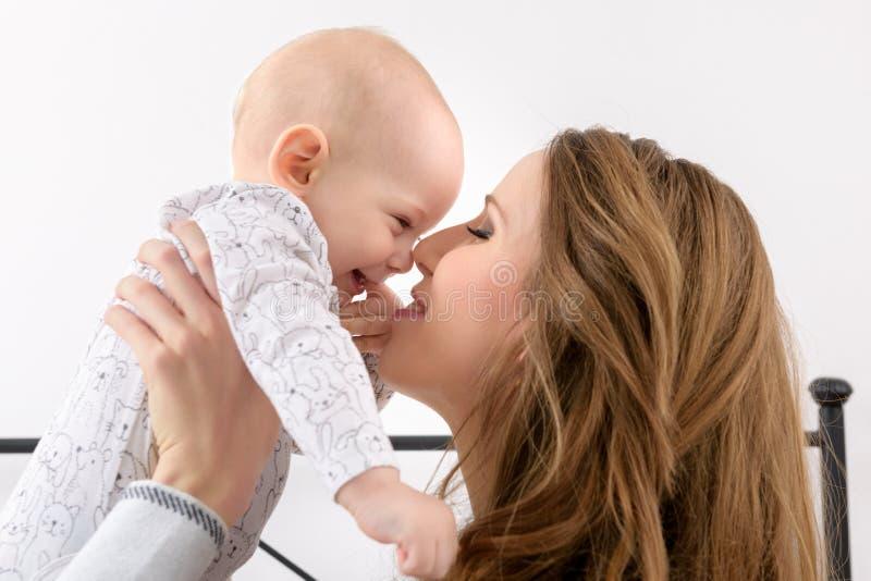 Gelukkige moeder en haar babyzoon die op een bed samen spelen Gelukkige Familie Moeder en pasgeboren kind stock afbeeldingen
