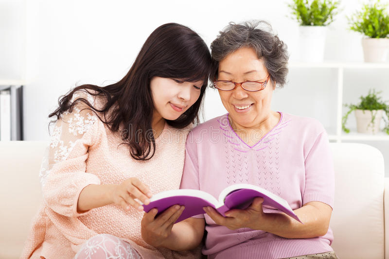 Gelukkige moeder en haar boek van de dochterlezing stock foto's