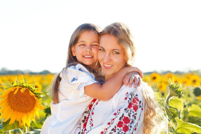 Gelukkige moeder en haar weinig dochter op het zonnebloemgebied stock fotografie
