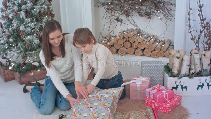 Gelukkige moeder en haar weinig zoon die omhoog Kerstmisgiften thuis verpakken royalty-vrije stock fotografie