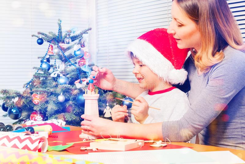 Gelukkige moeder en jongen die Kerstmisstuk speelgoed verfraaien royalty-vrije stock foto's