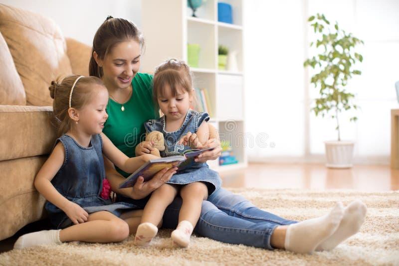 Gelukkige moeder en kleine dochters die een boek samen in de woonkamer lezen thuis het concept van de familieactiviteit royalty-vrije stock afbeeldingen