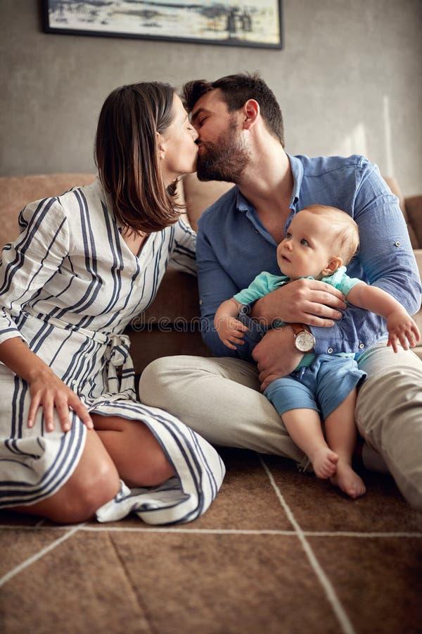 Gelukkige moeder en vader die hun babyjongen houden en bij ho kussen stock fotografie