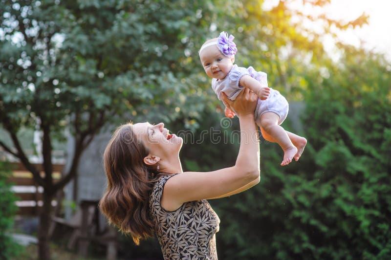 Gelukkige moeder en weinig babymeisje die in de de zomertuin rusten royalty-vrije stock fotografie