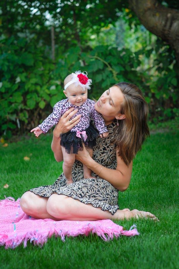 Gelukkige moeder en weinig babymeisje die in de de zomertuin rusten stock afbeeldingen