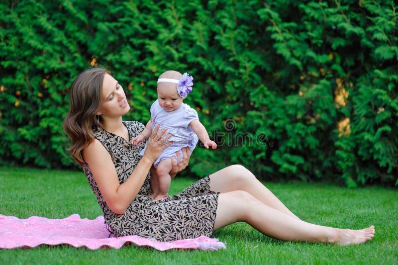 Gelukkige moeder en weinig babymeisje die in de de zomertuin rusten royalty-vrije stock foto's