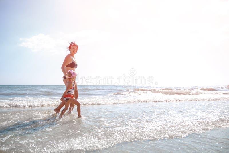 Gelukkige moeder en weinig die dochter op het strand bij zonsondergang in werking wordt gesteld stock fotografie
