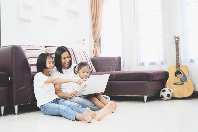 Gelukkige moeder en weinig dochter die een laptop computer met behulp van royalty-vrije stock afbeeldingen