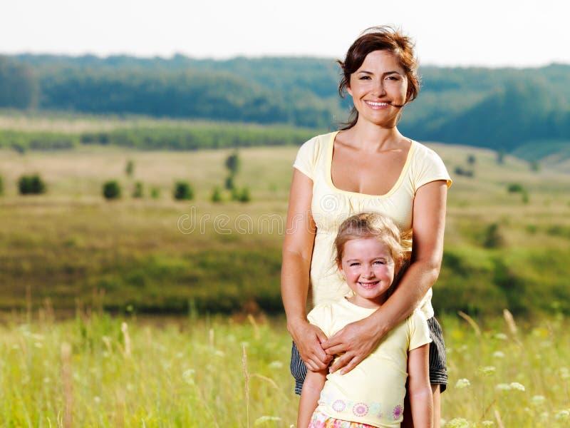 Gelukkige moeder en weinig dochter op aard stock afbeeldingen