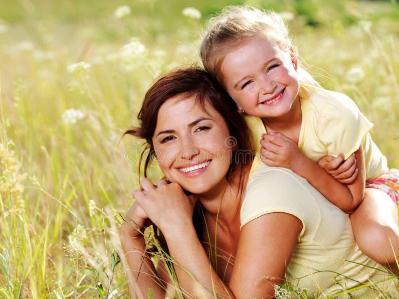 Gelukkige moeder en weinig dochter op aard stock fotografie