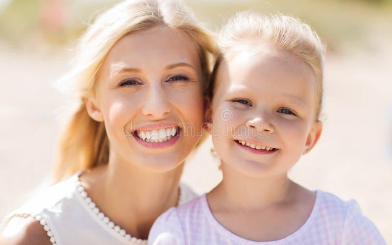Gelukkige moeder en weinig dochter op de zomerstrand stock fotografie