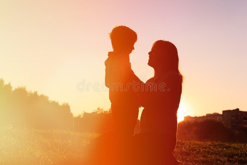 Gelukkige moeder en weinig zoon bij zonsondergang stock afbeelding
