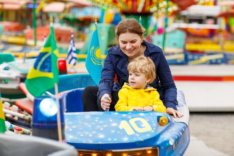 Gelukkige moeder en weinig zoon die op een carrousel berijden royalty-vrije stock afbeelding