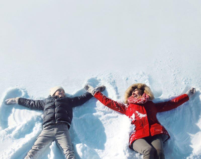 Gelukkige moeder en zoon die hebbend pret die samen in de sneeuwwinter liggen spelen royalty-vrije stock afbeelding