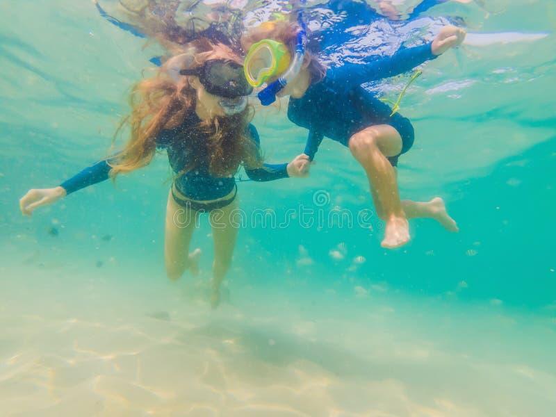 Gelukkige moeder en zoon die in het overzees snorkelen Bekijk de vissen onder water royalty-vrije stock afbeeldingen