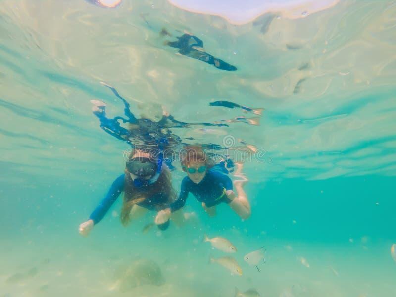 Gelukkige moeder en zoon die in het overzees snorkelen Bekijk de vissen onder water stock afbeeldingen