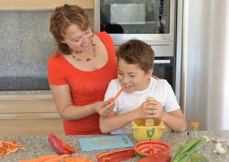 Gelukkige moeder en zoon die lunch met een mortier voorbereiden stock foto's