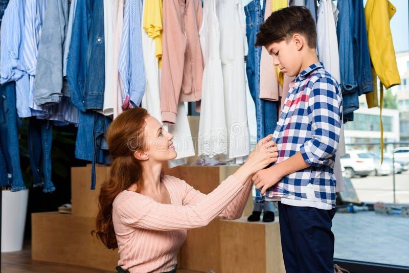 gelukkige moeder en zoon die in modieus winkelen stock foto's