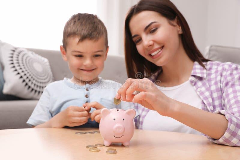 Gelukkige moeder en zoon die muntstukken zetten in spaarvarken royalty-vrije stock afbeeldingen
