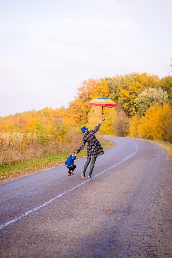 Gelukkige moeder en zoon die pret op de herfst hebben stock afbeelding