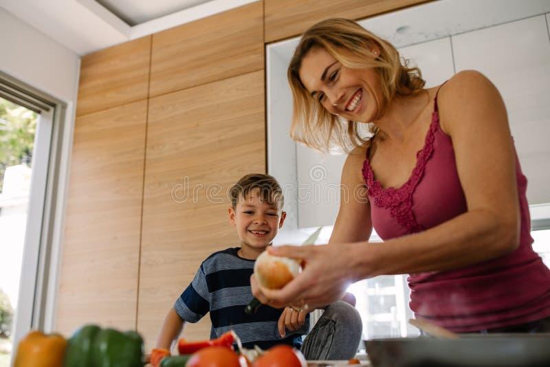 Gelukkige moeder en zoon die voedsel in keuken voorbereiden stock foto