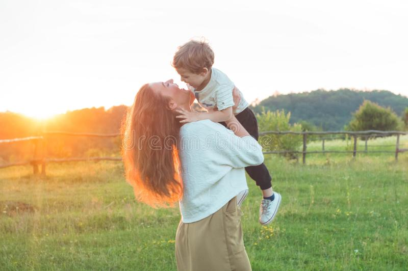 Gelukkige moeder en zoon op aard op zonsondergang Familie, kinderen en gelukkig mensenconcept stock fotografie