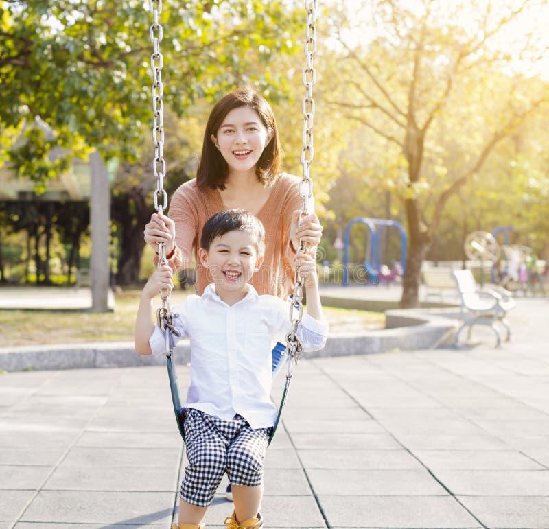 Gelukkige moeder en zoons speelschommeling stock fotografie