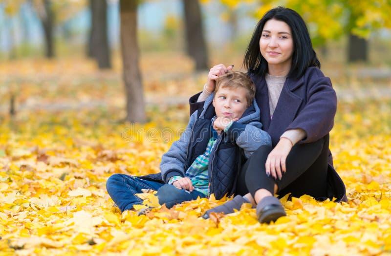 Gelukkige moeder en zoonszitting in gele dalingsbladeren royalty-vrije stock foto's