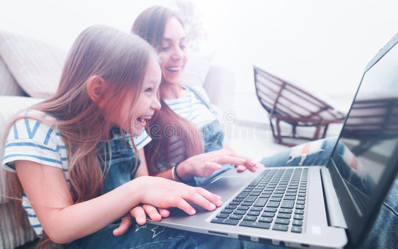 Gelukkige moeder met aanbiddelijk meisje met laptop royalty-vrije stock foto's