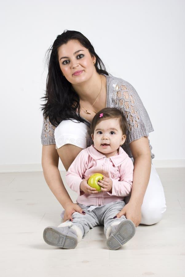 Gelukkige moeder met babymeisje dat een appel houdt stock foto's