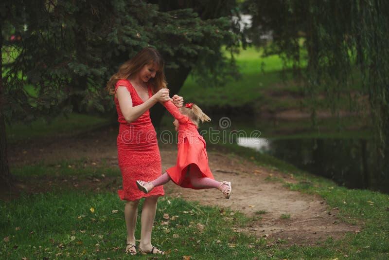 Gelukkige moeder met dochter in rode kleding stock afbeelding