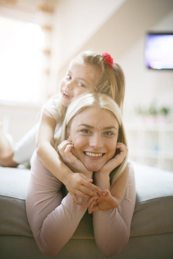 Gelukkige moeder met dochter thuis stock afbeeldingen