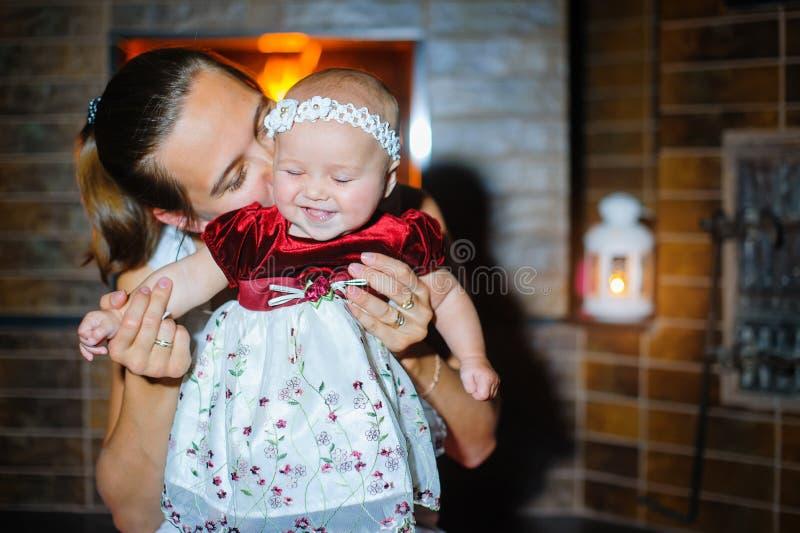 Gelukkige moeder met een babymeisje door de open haard in een kleding royalty-vrije stock fotografie