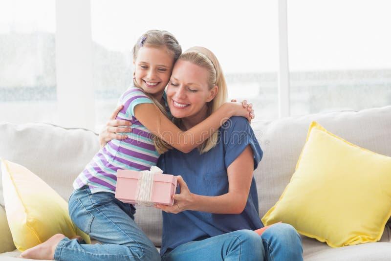 Gelukkige moeder met gift die dochter binnenshuis omhelzen stock afbeeldingen