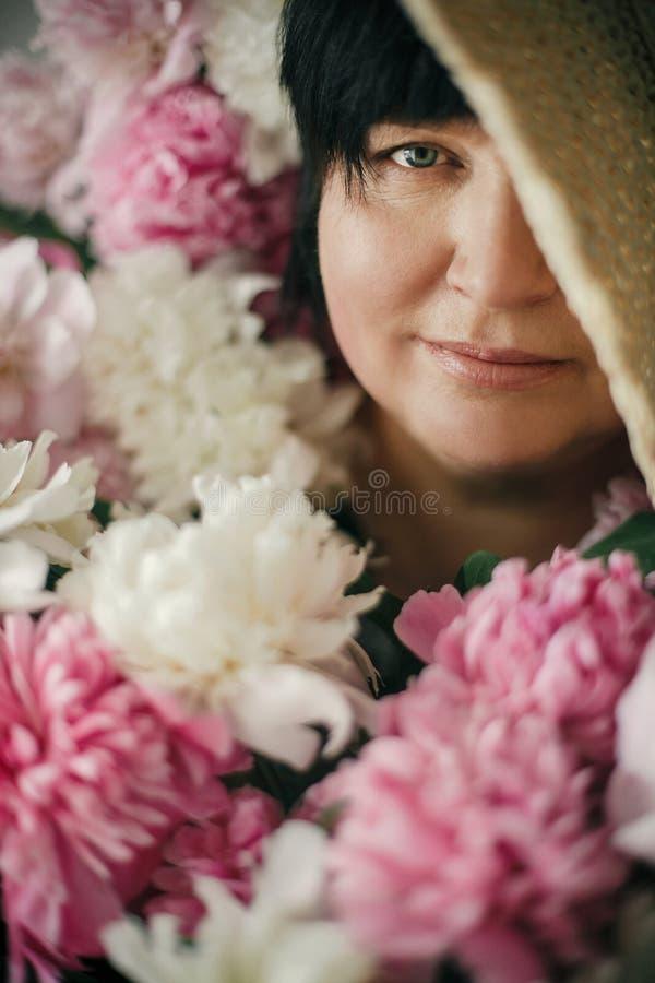 Gelukkige moeder met groot boeket van roze pioenen die van kinderen geven Het gelukkige concept van de moedersdag Mooie oudere vr royalty-vrije stock afbeelding