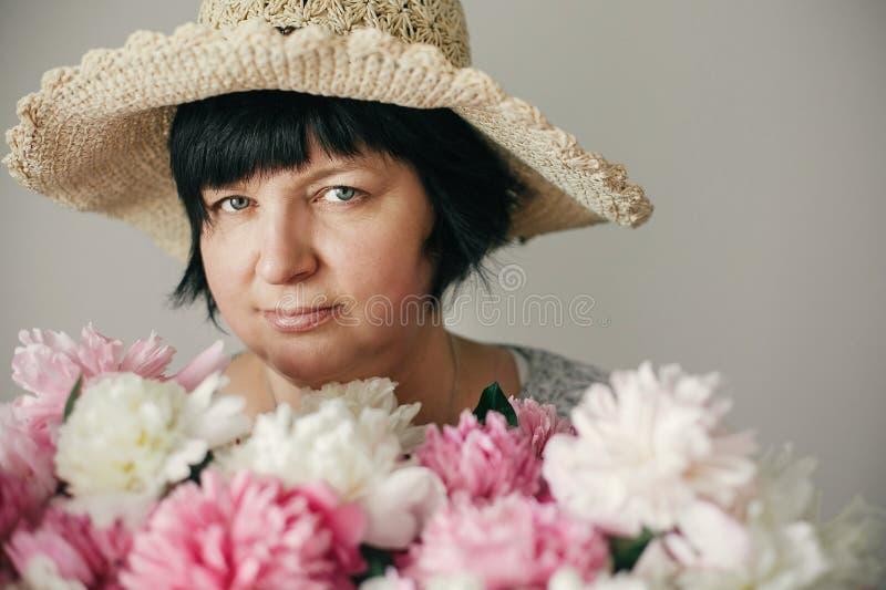 Gelukkige moeder met groot boeket van roze pioenen die van kinderen geven Het gelukkige concept van de moedersdag Mooie oudere vr royalty-vrije stock foto's
