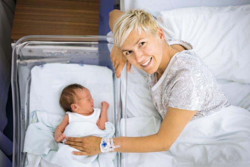 Gelukkige moeder met haar pasgeboren babyjongen nog in het ziekenhuis royalty-vrije stock afbeelding