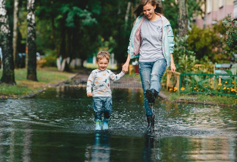 Gelukkige moeder met haar weinig zoon die regenlaarzen dragen die op grote vulklei na een regen in stadsstraat lopen stock fotografie