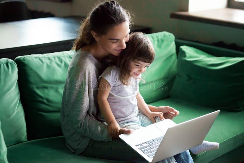 Gelukkige moeder met jong geitjedochter die pret online met laptop hebben stock foto's