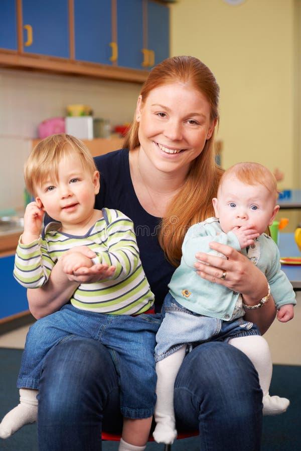 Gelukkige Moeder met Twee Jonge Kinderen bij Babygroep stock fotografie