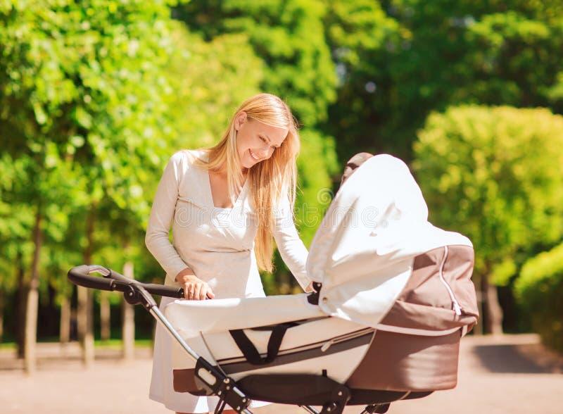 Gelukkige moeder met wandelwagen in park royalty-vrije stock fotografie