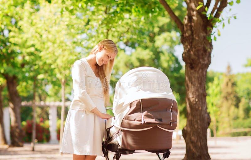 Gelukkige moeder met wandelwagen in park stock afbeeldingen