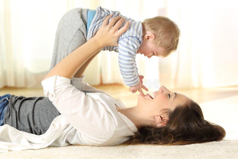 Gelukkige moeder op de vloer die haar babyzoon opheffen stock fotografie