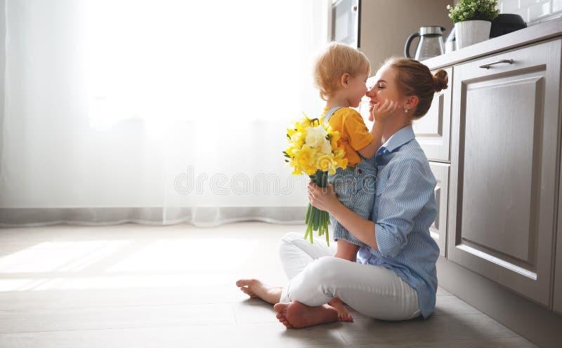 Gelukkige moeder` s dag! de babyzoon geeft flowersformoeder op vakantie stock afbeelding