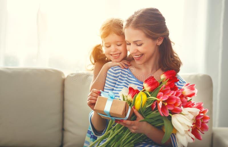Gelukkige moeder` s dag! de kinddochter geeft moeder een boeket van F stock foto's